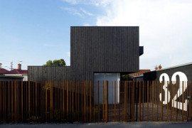 Dark-cladded facade sheltering bright interiors: Lily Street House