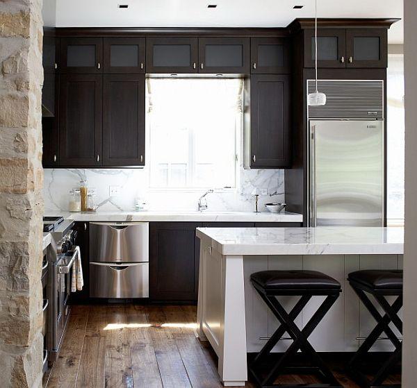 modern kitchen with stone walls, white island and dark cabinets
