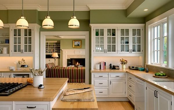 white kitchen cabinetry with wooden furnishings and green walls