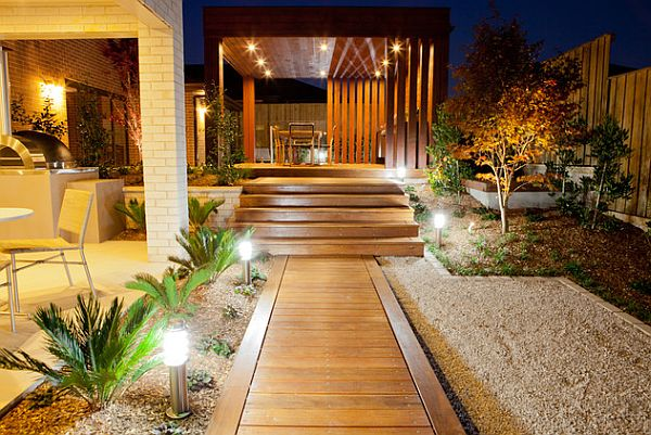 wooden deck walkway with stones and lighting