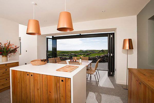 Modern Stone Hut – white kitchen with wood accents