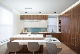 Kitchen with walnut-veneered cabinetry and white furniture