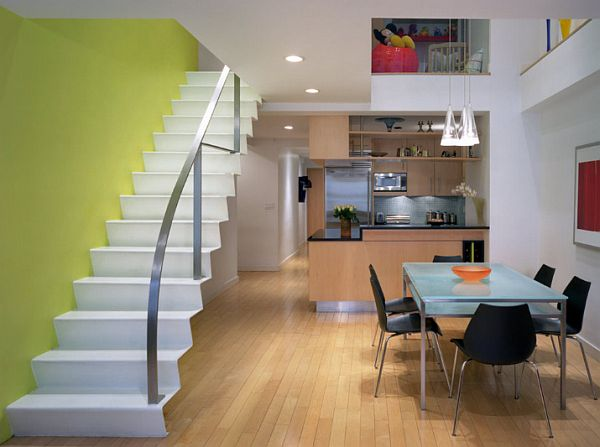 NYC loft with modern design and yellow wall behind the white staircase