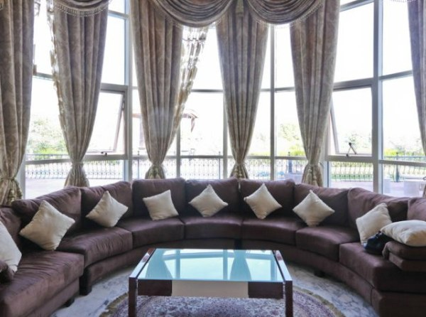 Ornate draperies and a plush sectional sofa