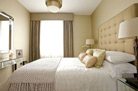 Feminine bedroom design with neutral colour scheme and quilted headboard