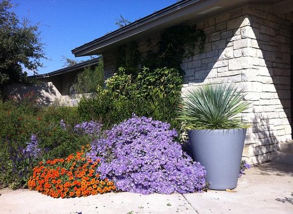 Purple and orange flowers line a garden pathway