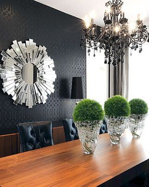 A black themed living room with a sunburst mirror with an artistic touch
