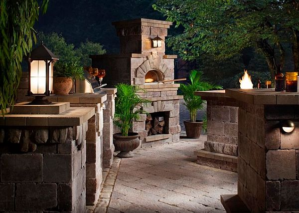 outdoor kitchen with pizza oven and stone tables