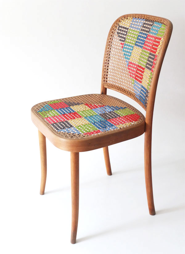 A cross stitched cane chair