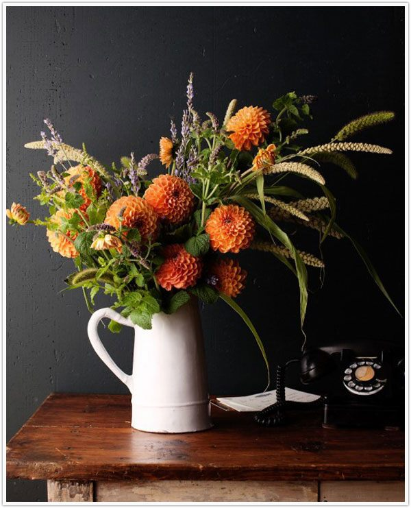A fall centerpiece in a pitcher vase