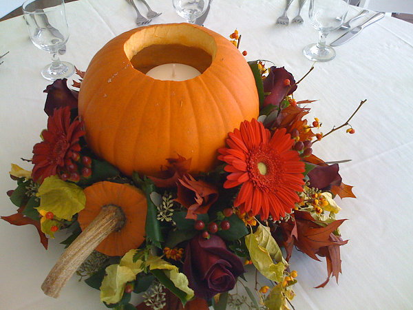 A fall centerpiece with flowers and a pumpkin