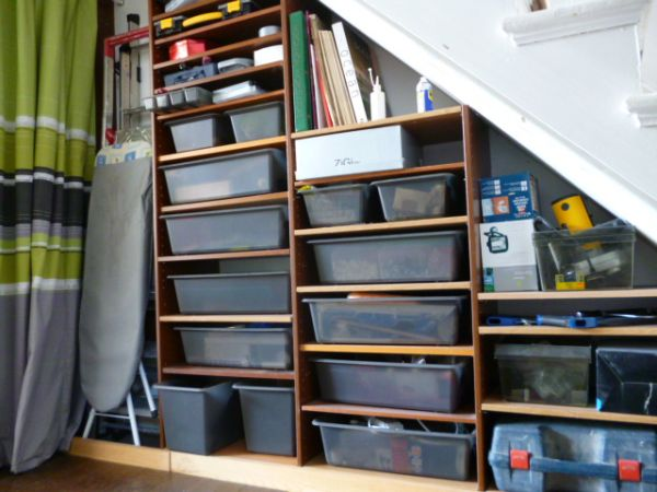 Storage shelves under basement stairs