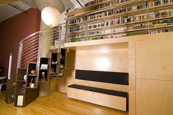 Large storage shelf space under modern metallic stairs