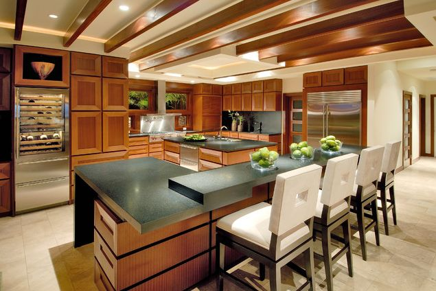Modern wooden kitchen with chairs at the eat in counter and wine fridge