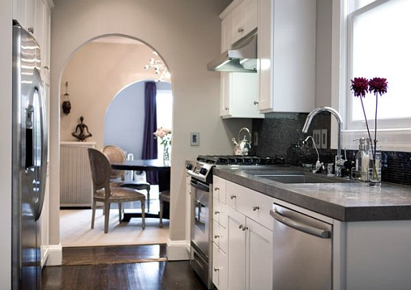 Small kitchen with taupe wall, dark floors, gray counters and white cabinets