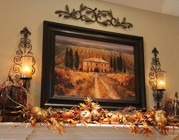 Fireplace mantle serving as a fancy shelf for autumn decorations, along with pictures and lampshades