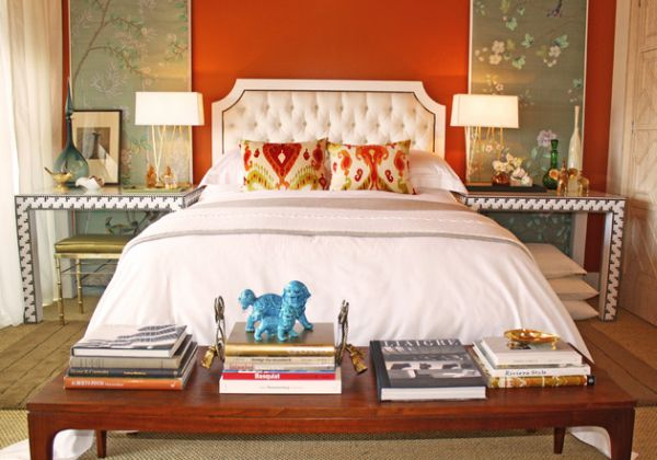 Beautiful tufted headboard stands out in this eclectic bedroom adored by orange hues