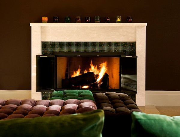 Emerald pillows, a brown sofa and brown walls with a white mantle fireplace