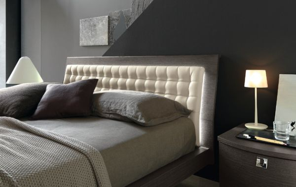 Gentle back light illuminates this slanting tufted headboard for a semi minimalist bedroom