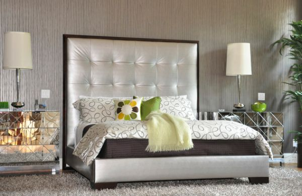 Silver upholstered bed with a tall tufted headboard
