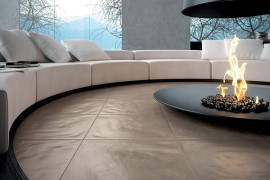 A circular living room sofa with a modern fireplace