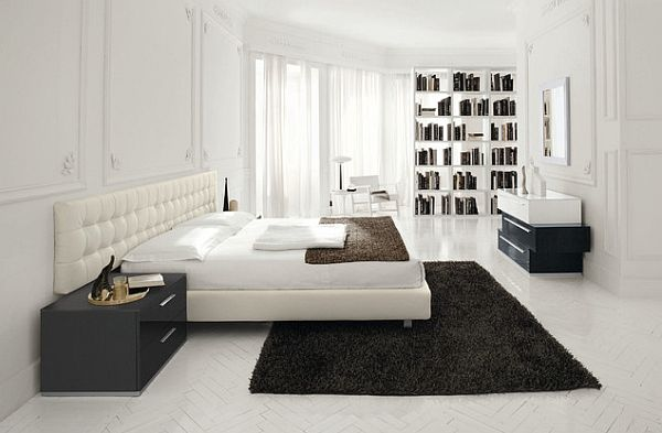 sleek white bedroom with dark colored rug for contrast