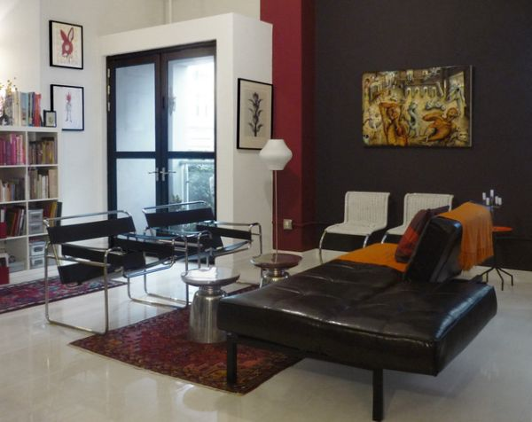 Compact modern loft in dark tones with Wassily chairs that match the couch