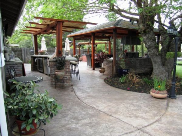 A spacious patio design with a covered seating area