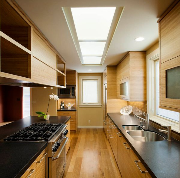 Dark countertops with light cabinets and smart skylights grace this