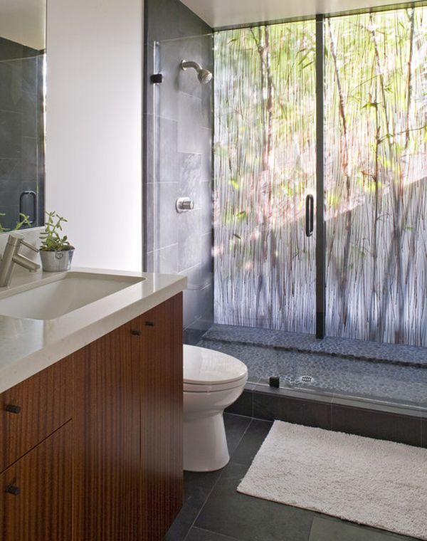 Dramatic bathroom with beautiful backlit rainforest-like acrylic panel and glass doors