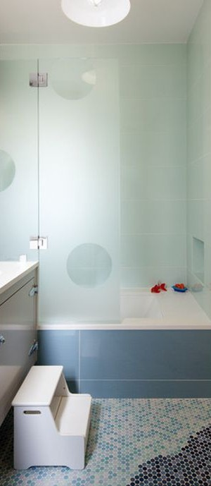 Imaginative transluscent glass enclosure creates a vibrant look in cool blue for the kids' bathroom
