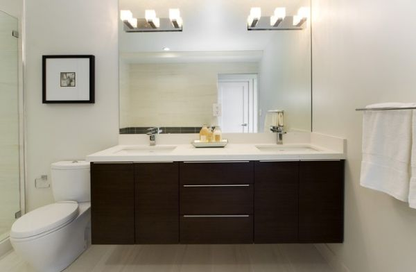 white countertop and dark cabinetry make this bathroom vanity stylish and beautiful bathroom mirror and lighting ideas