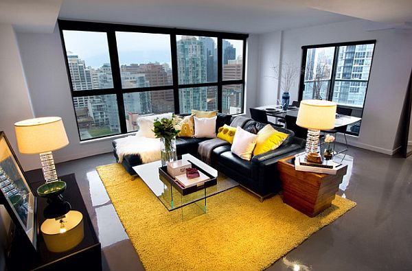 Living room with black couch in contrast with a yellow rug