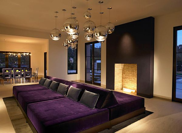 Stylish rec room with purple double couch and a fireplace