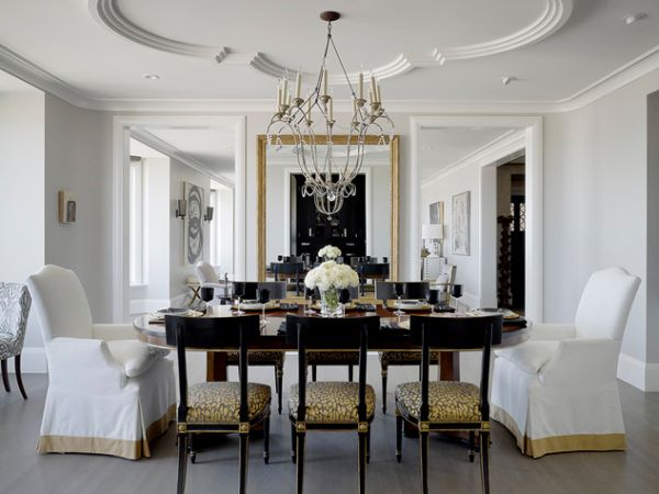 Artistic ceiling design and lovely chandelier give this dining room in neutral tones a classic look