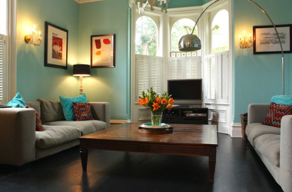 Eclectic blue living space showcases classy use of shutters