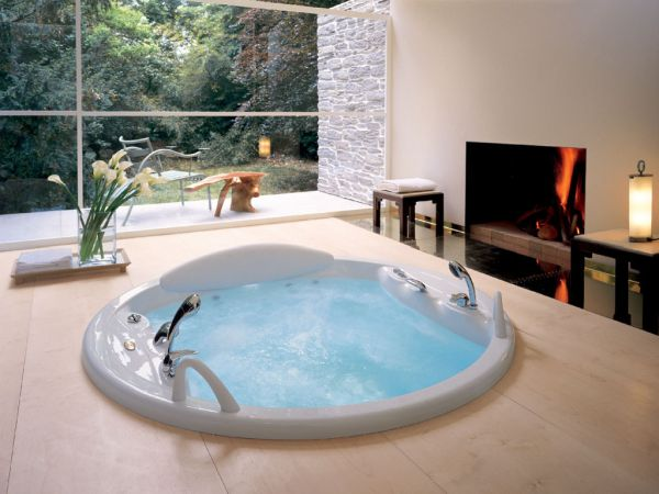 Modern jacuzzi next to a beautiful fireplace