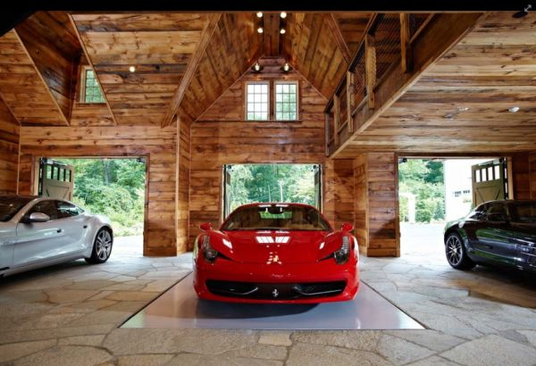 Reclaimed chestnut and pine lumber walls with natural stone flooring grace this spacious garage