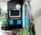 Colorful front entry with blue door and pillows on a bench
