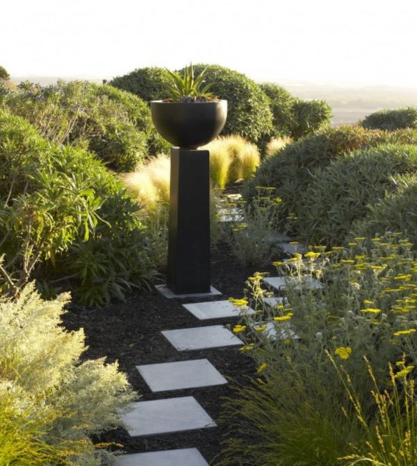 Beautiful pathway of stones and a gorgeous plinth with a bowl on top standout in this garden