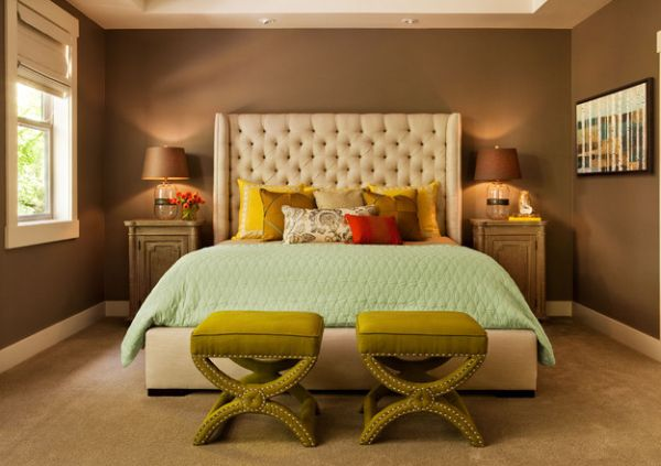 Bedroom in dark hues with a couple of luxurious benches at the foot of the bed