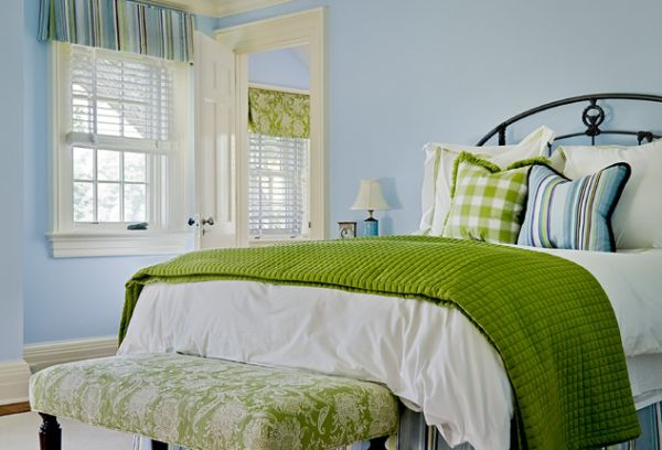 Bedroom in green sports a bench with fabric similar to one use for a Roman shade in the room