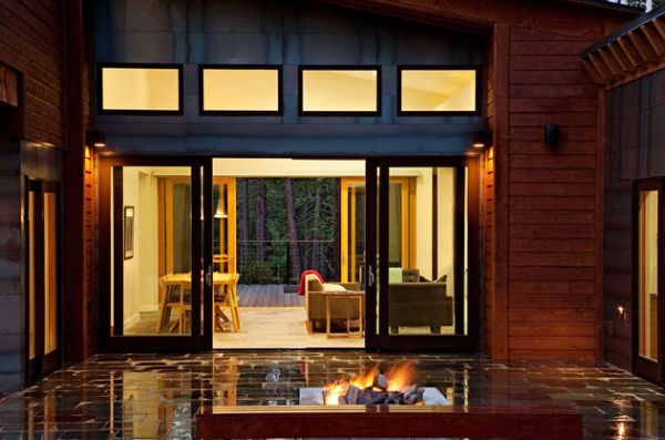Cool sliding doors between living space and patio with modern fireplace