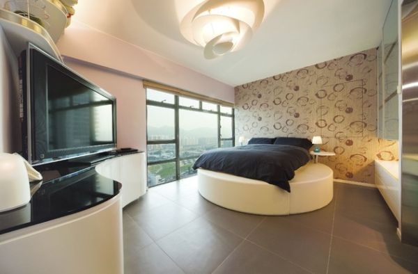 Curved cabinets and innovative lighting compliment the plush round bed