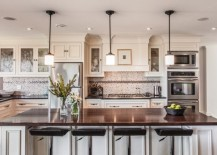 Dazzling pendant lights above a white kitchen island with dark granite top