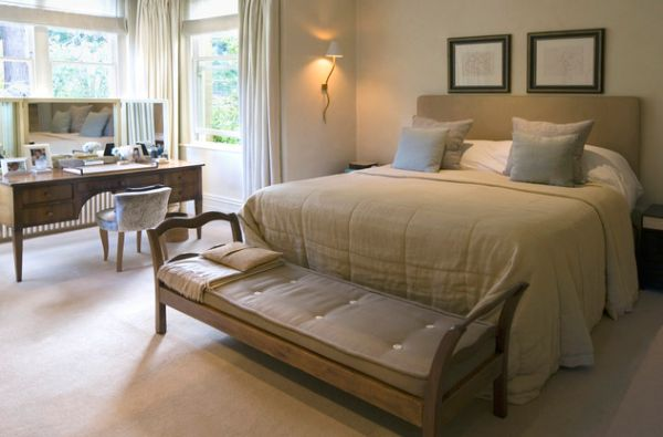 Elegant bedroom with a simple bench at the foot of the bed