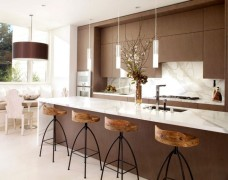 Exquisite modern kitchen in white and brown with sleek pendant lights above the kitchen island