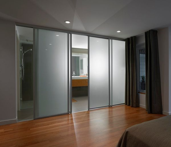 Frosted glass sliding doors separate the contemporary bedroom from the ...