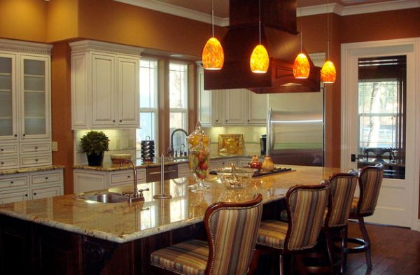 Luma pendant lights with an orange hue complement the rest of the kitchen