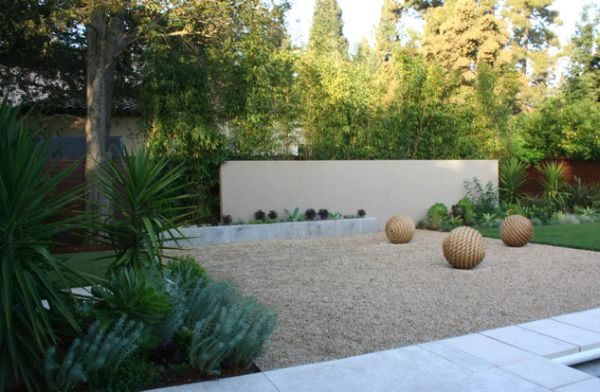 Open rock area with sculptural balls complements all the green around it elegantly